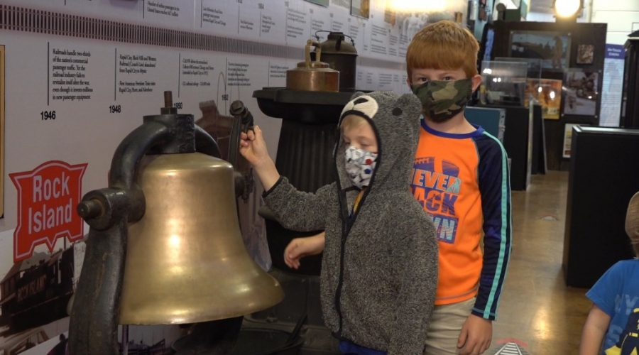 Two boys in front of bell displayed at 1880 train museum