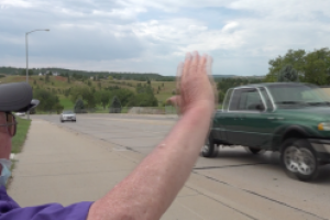 Holiday Hills Estates resident waves to traffic to brighten the day of drivers
